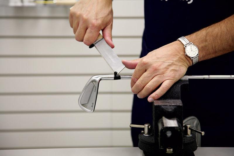 Kỹ thuật viên thay shaft gậy golf chính xác với máy hỗ trợ